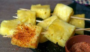 Fresh pineapple chunks on skewers, dusted with chili, salt, and lime.